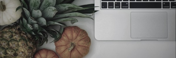 A pineapple some pumpkins and a computer