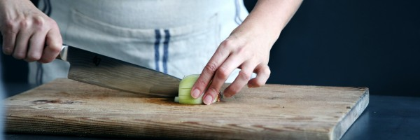 Chef cutting an onion on a wooden chopping board